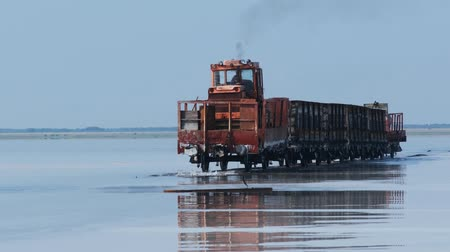 Old train rides on the railway laid in the water through the salt lake. train travels from water. Mined salt in Lake Burlin. Altai Bursol. Russia. August 2019