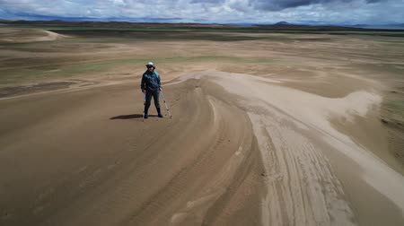 Drone fly around a tourist standing on top of sandy barkhan. Sandy desert Mongol Els in western mongolia