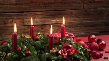 arife : Four burning red candles on a white background. Christmas tree in front of a rustic wooden wall. Close-up time. approx. 27 sec.