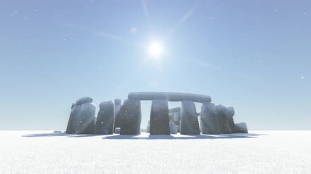 equinox : Stonehenge covered with snow falling from the sky with the sun shining mysteriously above. The video can be used to symbolize the climate changes due to global warming