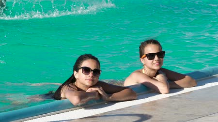 irmãs : Two pretty girls are swimming in the pool. Stock Footage