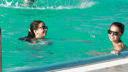 irmãs : Sisters are swimming in the pool.