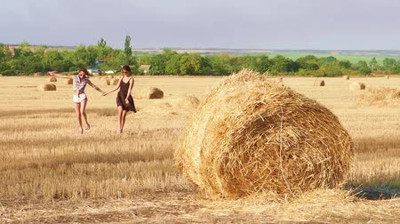 bales : Two cute girls run across the field with a beveled straw. Slow motion.