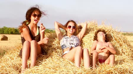 szénaboglya : Two cute girls and a little boy play on a haystack. Slow motion.
