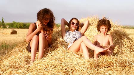 bales : Two cute sisters and a little brother playing on a haystack. Slow motion.