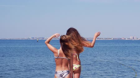 mayo : Two young pretty girl in a bikini walk on a pier on the background of the sea. Slow motion.