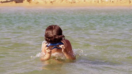 mascarar : A curly-looking pretty boy in a scuba diving mask dives into the water. Slow motion.