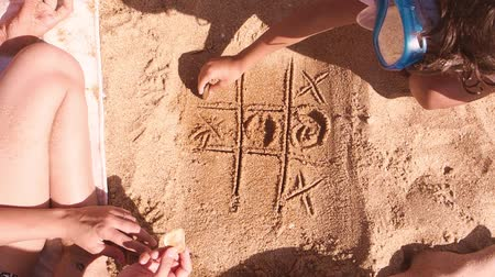tık : Two sisters and a little brother play tic-tac-toe on the sand on the beach. Slow motion.