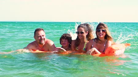 colchão : Happy family of four on vacation at sea shore. Happy family with yellow mattress bathes in sea. happy mum daddy and two children play in water. Slow motion