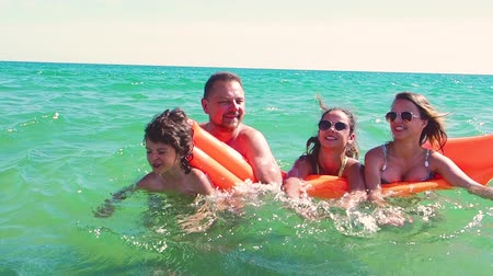 матрац : Happy family of four on vacation at sea shore. Happy family with yellow mattress bathes in sea. happy mum daddy and two children play in water. Slow motion