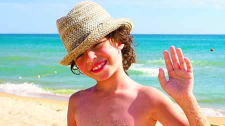 calções de banho : a happy young child waving and waving at the beach by the ocean shore. slow motion