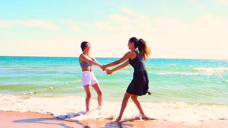 friendship dance : Two funny girls spinning holding hands against the background of the sea. Summer sunny day on a sandy beach. Slow Motion