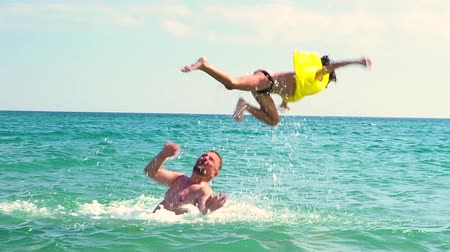 skok : Dad throws up his son in an inflatable life jacket in the sea. Safety Concerns and Parental Care Concept. slow motion