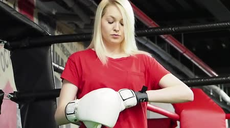 construct : woman wearing boxing gloves sitting near ring. woman on white boxing gloves. Feminism, girl power, fight, gender, woman rights concept. slow motion