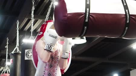 átlyukasztás : Young woman making punching bag on a punching bag.sexy fighter girl wearing white panting boxing bag in gym. slow motion Stock mozgókép
