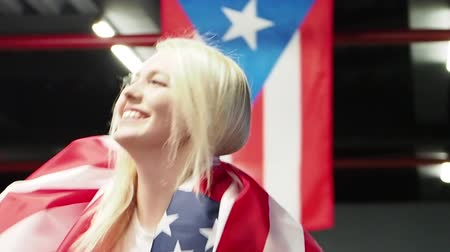 パトリオット : Success woman celebrating her success with the flag of USA. Female boxer with flag Patriot and fan concept. slow motion 動画素材