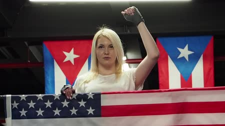 participante : Success woman celebrating her success with the flag of USA. Female boxer with flag Patriot and fan concept. slow motion Vídeos