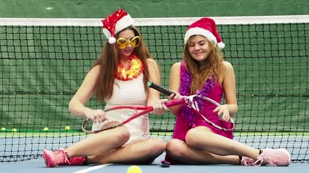 bêbado : Two sexy brunette girls in glasses sitting on the court. Celebrating the new year during a sporting event. Sporty girls Christmas. slow motion