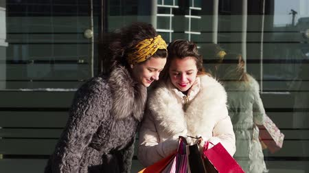 consumerism : Group of happy friends shopping in the city. Shopping and tourism concept- beautiful girls with shopping bags. The girl shows the purchases to her sister. slow motion