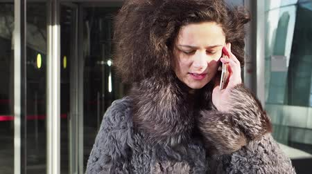 antipatico : Cheerful woman talking on the phone. Pretty woman in winter clothes worn in winter clothes. Slow motion