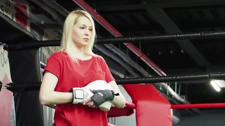 бокс : Beautiful woman training boxing blows with punchbag in the gym. Blonde strong athlete in white boxing slow motion Стоковые видеозаписи