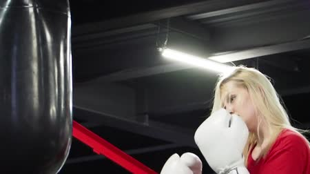 kayış : handsome female athlete boxer on training. The girl is engaged in boxing gloves. Dress up boxing gloves. Preparing for battle. Reflections before the fight. slow motion