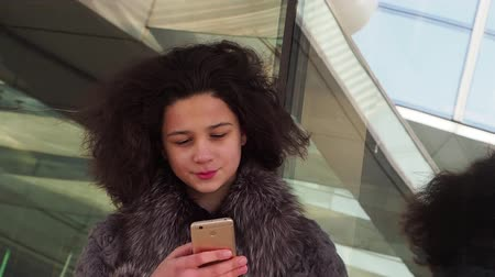 calling telephone : Cheerful woman typing on the smartphone. Beautiful woman in winter clothes Slow motion