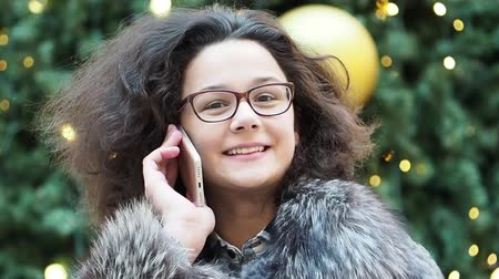 x mas : Holidays, communication and people concept - portrait of a beautiful young woman Slow motion
