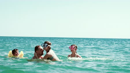 4K Family on vacation. Happy father with daughters and little son in the sea. Slow motion Vídeos