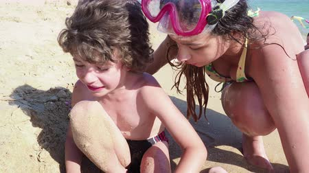 4K Little boy cries and screams. Elder sister comforts younger brother crying on sunny sandy beach Slow Motion Vídeos