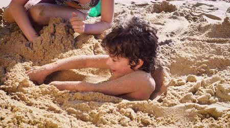 gömülü : 4K Happy family having fun at the beach, burying little boy in the sand. Slow motion