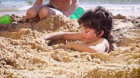 buried : 4K Happy family having fun at the beach, burying little boy in the sand. Slow motion