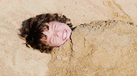 4K A little toddler boy is buried in the sand on a beautiful ocean beach
