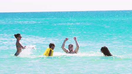 4K Happy family of four in vacation at sea shore. happy mum daddy and two children play in water.