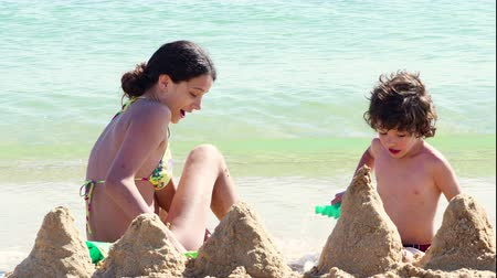 4K Children make a castle of sand on the beach. Two siblings of different ages, brother and sister, sitting close to the sea and digging in the sand on hot day at the beach