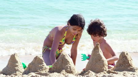 saçlı : 4K Children make a castle of sand on the beach. Two siblings of different ages, brother and sister, sitting close to the sea and digging in the sand on hot day at the beach