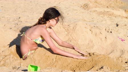 pštros : 4K A beautiful teen girl is buried in the sand on a beautiful ocean beach Dostupné videozáznamy