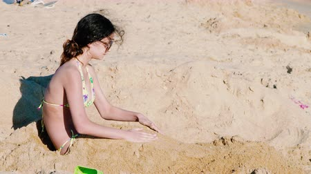 4K A beautiful teen girl is buried in the sand on a beautiful ocean beach Vídeos