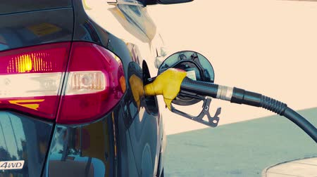 пистолеты : Fuel nozzle inserted in cars gas tank as its being refueled at gas station pump on a sunny day. Closeup, 4K