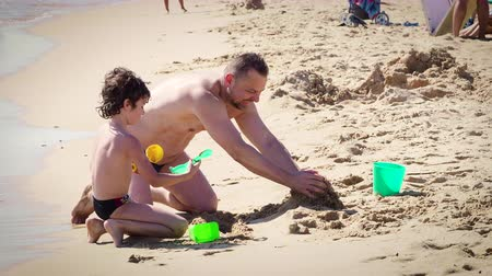 4K. A dad and little son build a sand castle on the coast