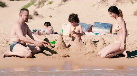 4K Happy family. Father playing sand with Cute Smiling little boy child and daughter on white sand beach on nature outdoor, Family travel, summer beach vacation with children concept.