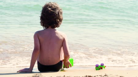 hét : 4K Back view of a young boy playing happy at the beach after the end of school. Child waiting waves on the seashore. Stock mozgókép