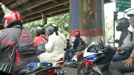 Motorcycles and cars are on the road in Jakarta, Indonesia