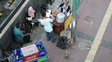 View of street food on the sidewalk in Bundung, Indonesia. People and street food vendors are around the area.