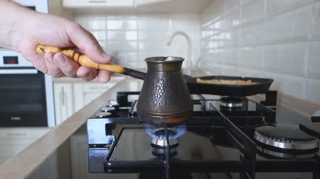 caffe : the man put the bowl of coffee on a gas stove fire