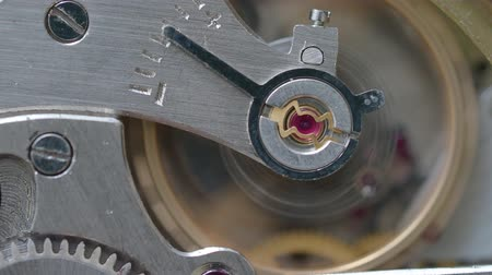 pinion : macro shooting - movement of running vintage steel mechanical watch with focus on ruby ??stone on foreground