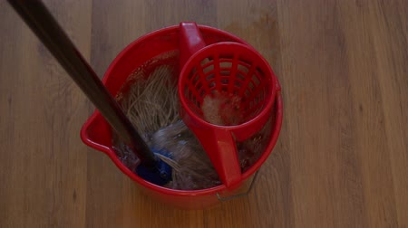nemli : top view of cotton mop is rinsing in red bucket with detergent on wooden laminate floor Stok Video