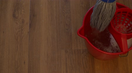 laminált : cotton mop cleans a wooden laminate floor near a bucket with detergent at home Stock mozgókép