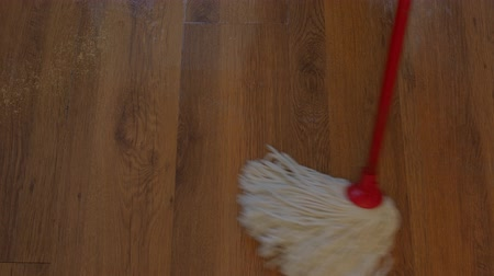 laminált : white cotton mop cleans a wooden laminate floor at home Stock mozgókép