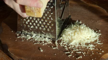 grating : woman finishes grating a Parmigiano Reggiano cheese on grater close up in rustic kitchen illuminated by sun Stock Footage